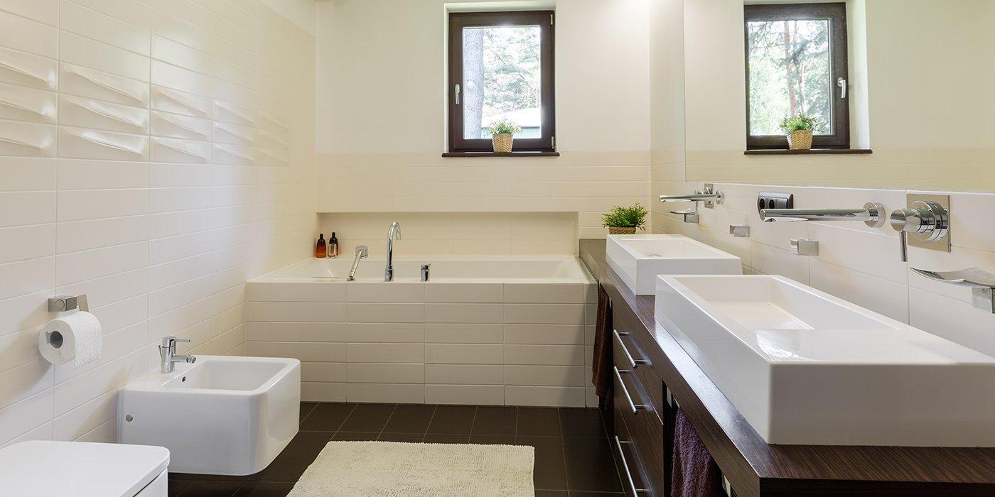 Un bagno minimal con due lavabi e una vasca