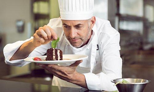 un cuoco che decora un piatto con un dessert