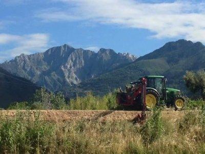 trattore con sfondo montagna e cielo blu