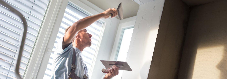 operaio mentre lavora in una casa per intonacatura interna