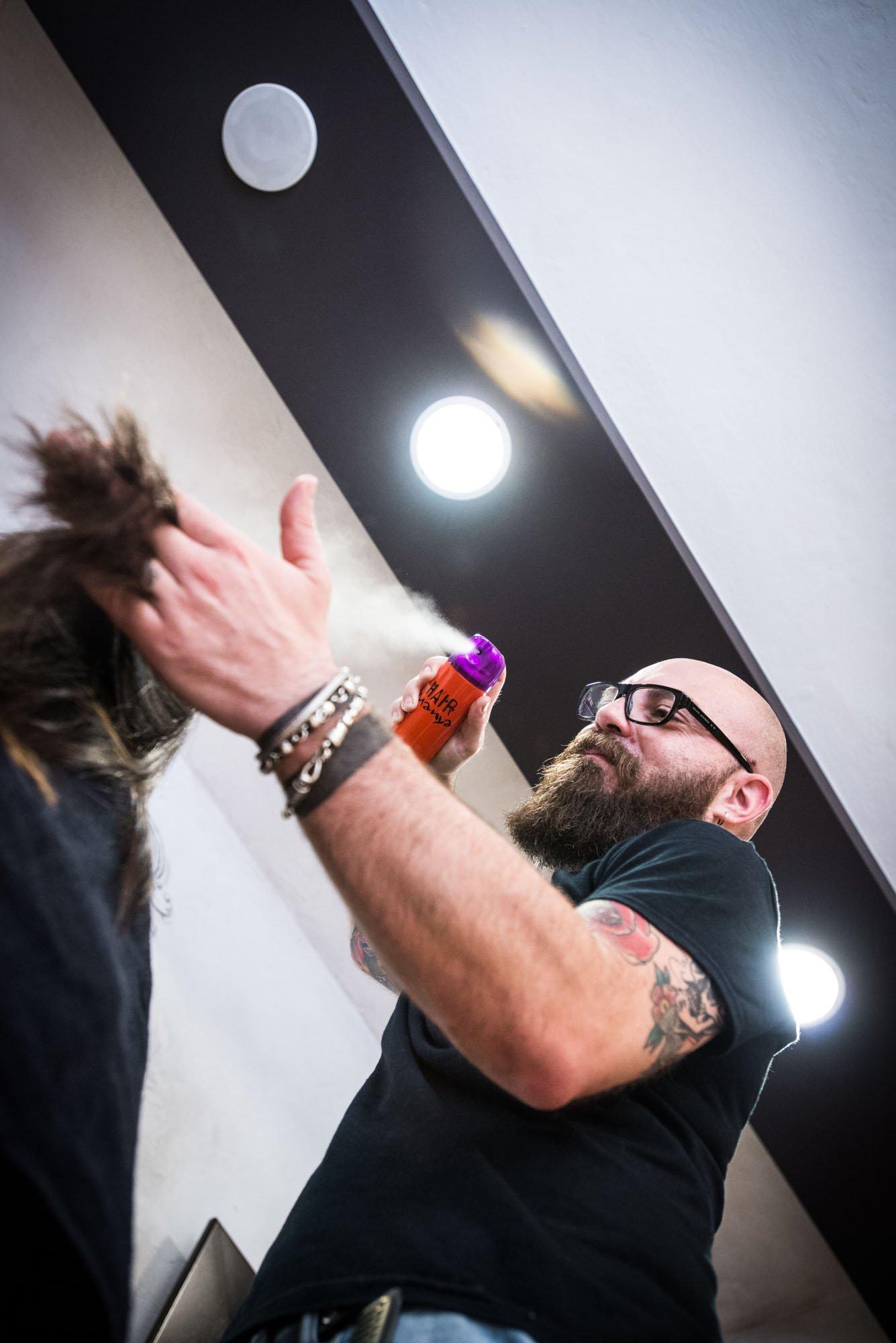 parrucchiere da la lacca nei capelli di una cliente