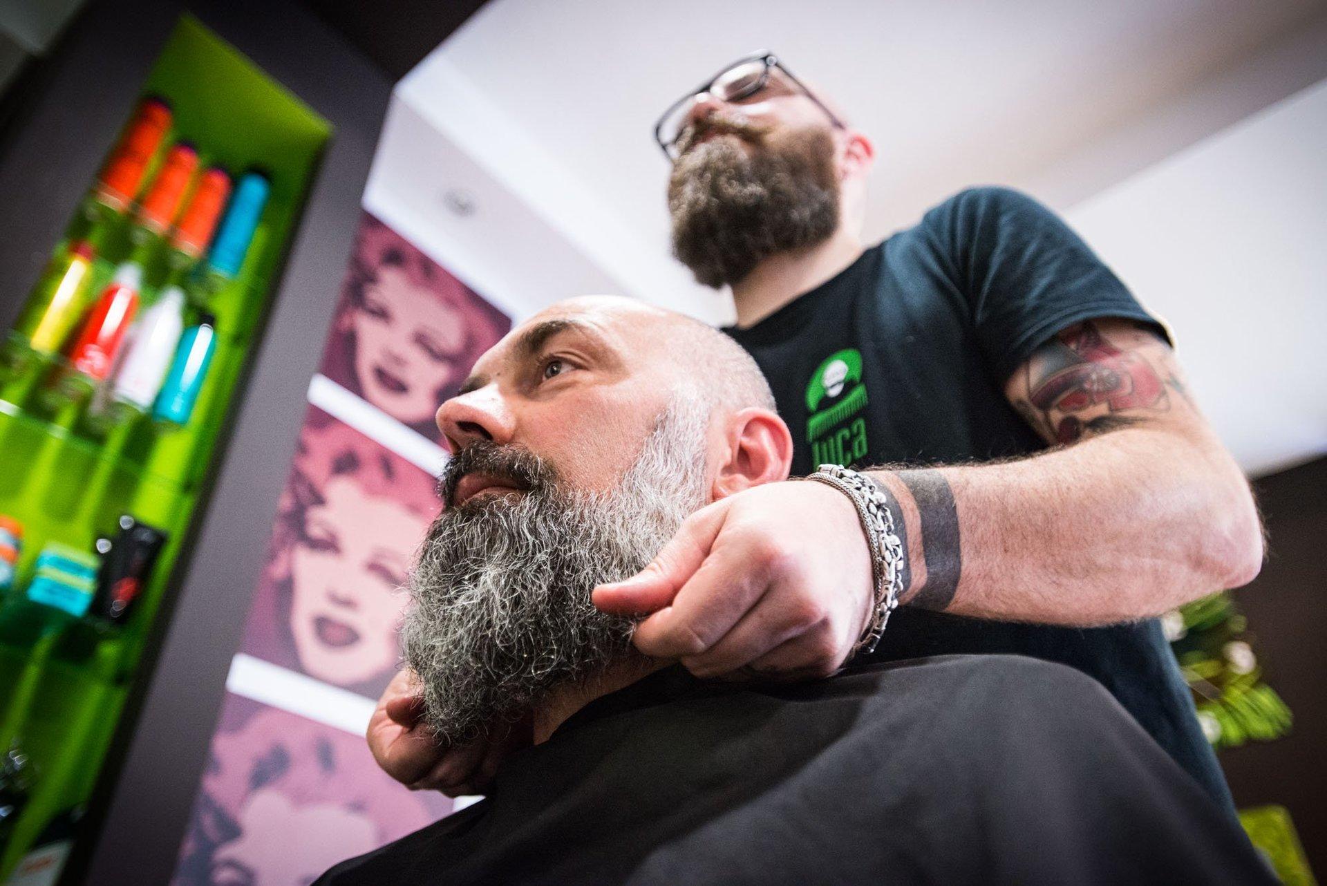 mani del parrucchiere mentre sistema la barba di un cliente