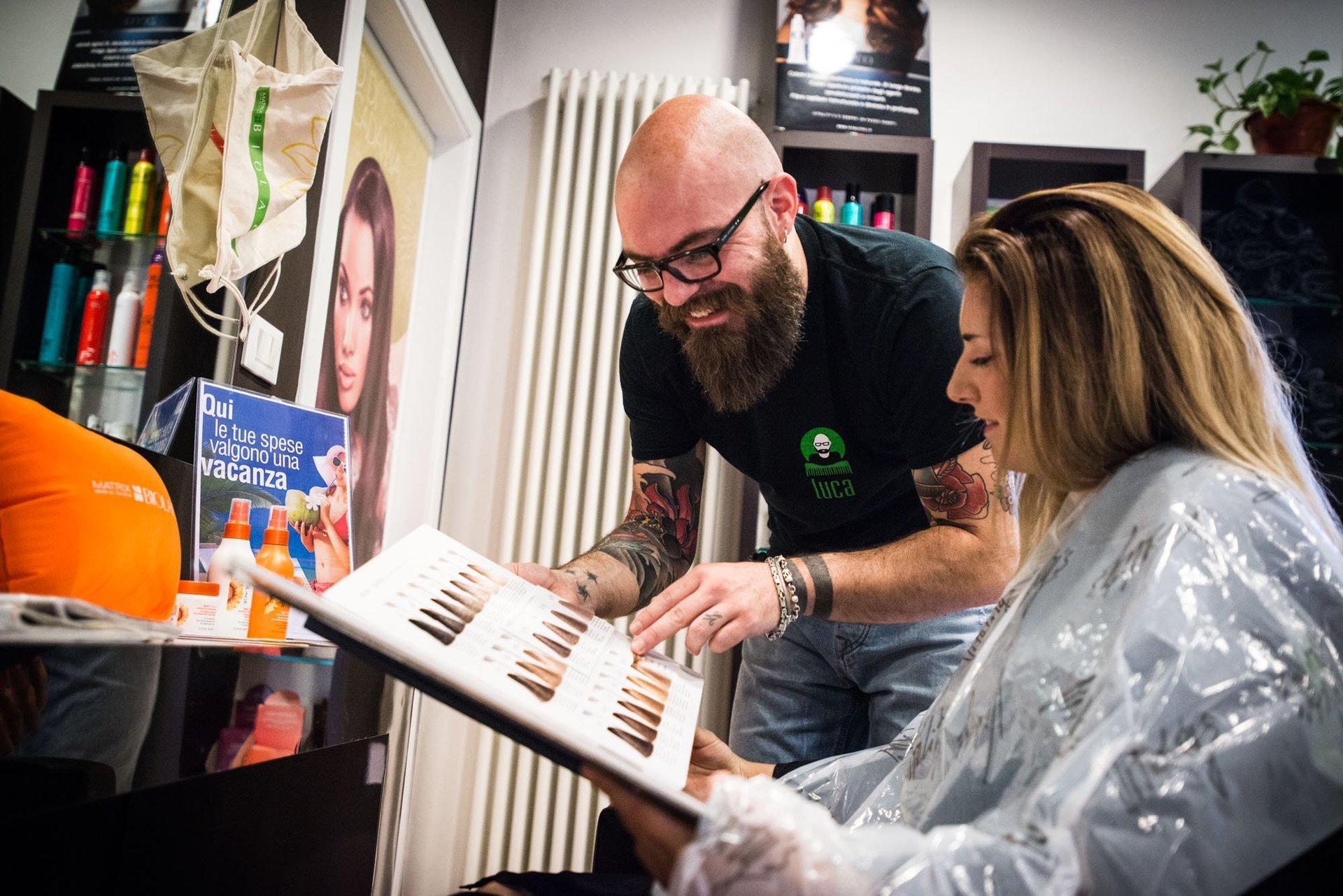 parrucchiere mostra il catalogo delle tinte a una cliente