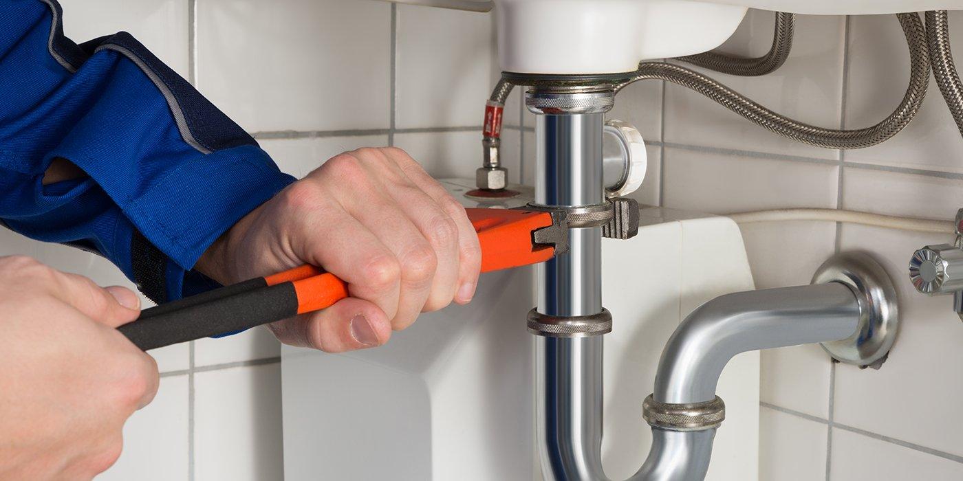 due mani di un idraulico che con un attrezzo stringe un tubo di un lavabo