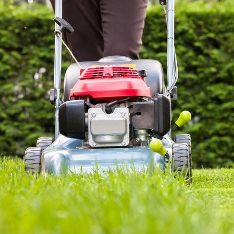 A worker maintaining the grounds with lawnmower