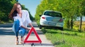 auto ferma su ciglio strada, ragazza che posiziona triangolo, strada alberata