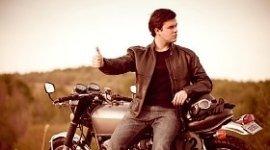 motociclista che fa l'autostop, moto in panne, campo incolto di sfondo