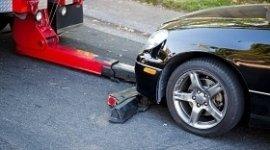 acrro attrezzi che sta caricando un auto, auto nera in panne, braccio del carro attrezzi che aggancia la macchina