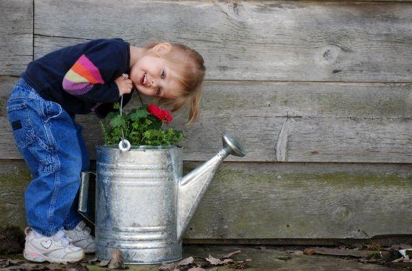 bambina di fianco a fioriera nel giardino dell'agriturismo