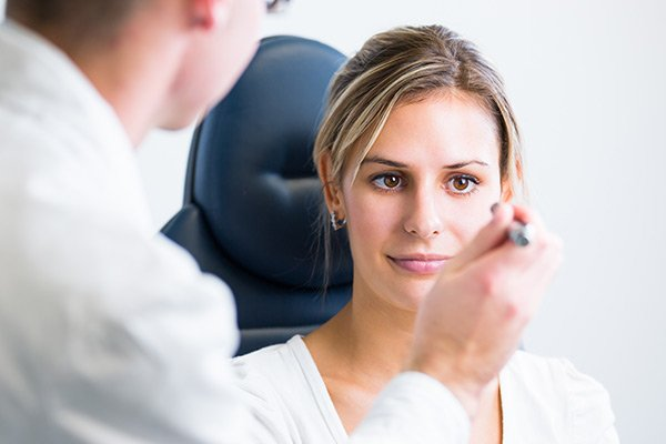 Pretty young woman having her eyes examined by an eye doctor-Greensboro, NC