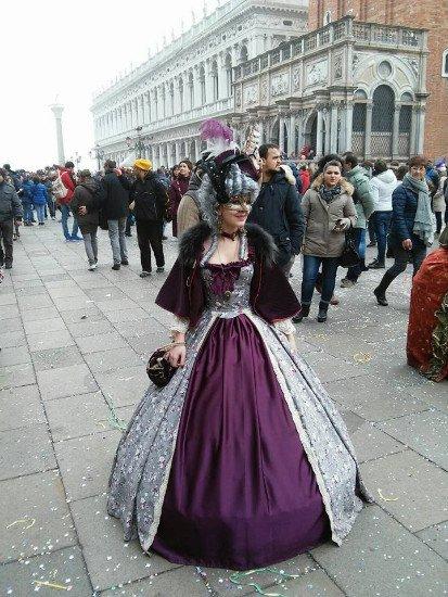 una donna con un vestito viola, argentato e una maschera