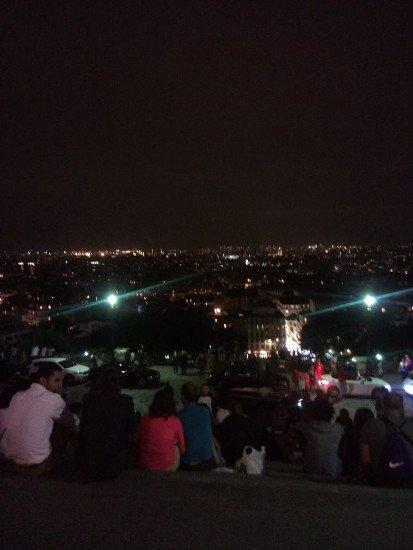 delle persone sedute che guardano la città di sera