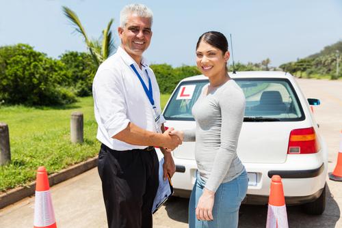 istruttore di guida stringe la mano ad una ragazzina che ha passato l'esame di guida