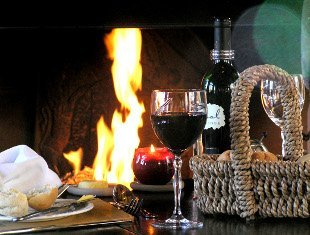 Glass of red wine on a table in front of a roaring fire