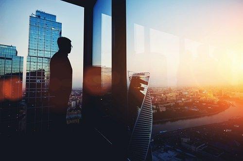 Uomo guardando la città dalla finestra