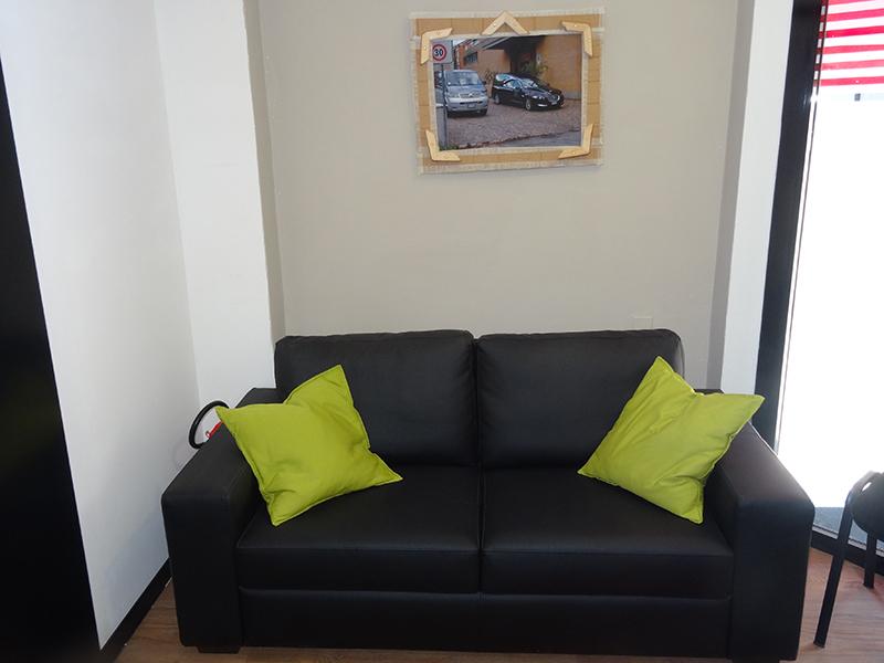 Un divano di pelle da due posti con due cuscini verdi e sul muro un quadro con l'immagine di due carri funebri