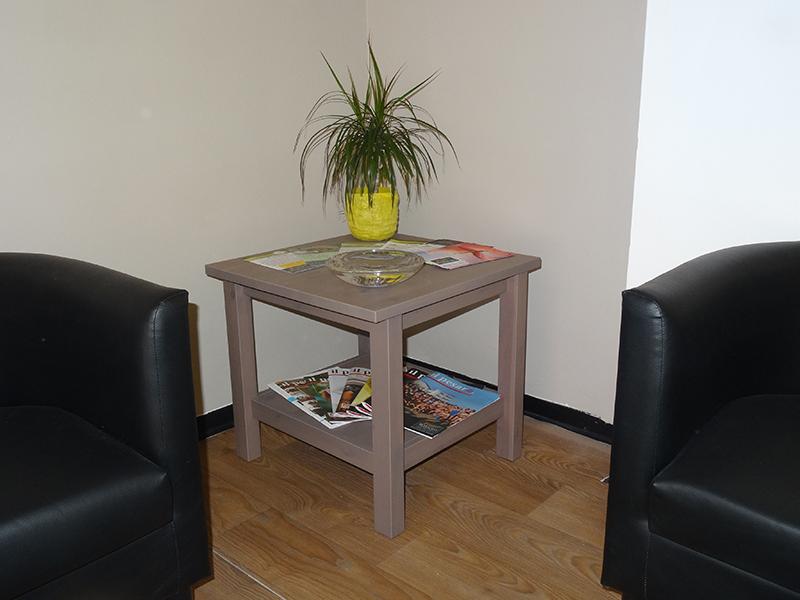 Due poltrone nere di pelle e un tavolino con un vaso con una pianta a forma di ananas