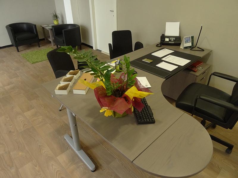 Una stanza con una scrivania angolare con tre poltrone e infondo due poltrone di pelle e un tavolino in angolo