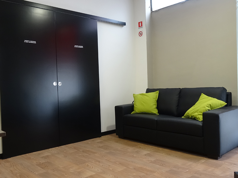 Un divano di pelle a due posti e sulla destra un'entrata con due porta di legno scorrevoli