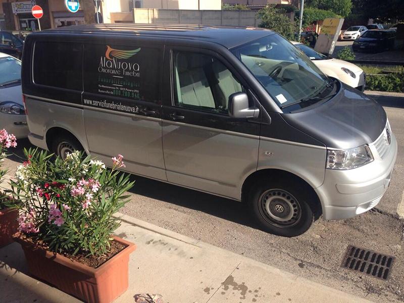 Un carro funebre parcheggiato sulla strada  con scritta Ala Nuova Onoranze funebre, funerali ecologici