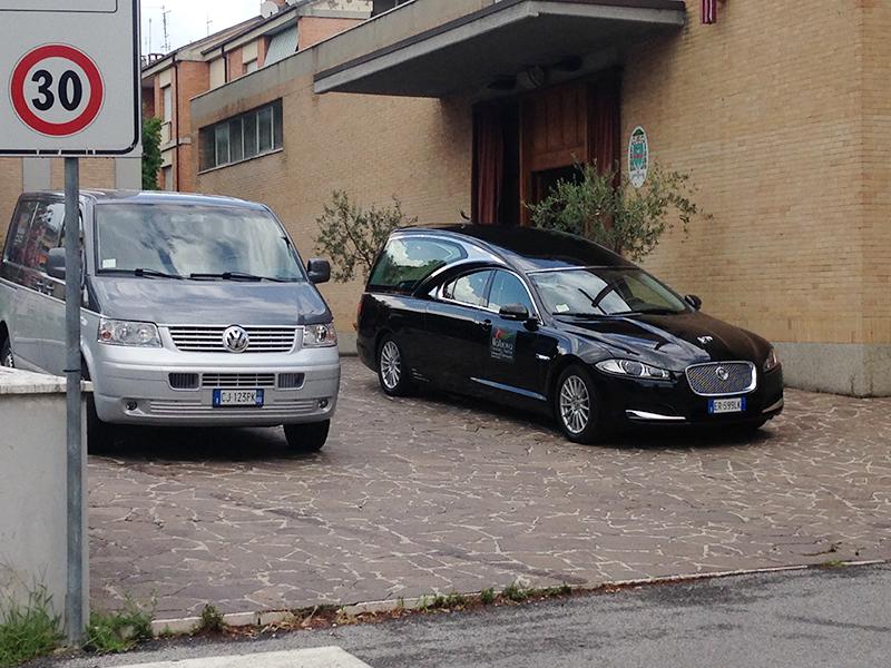 Due carri funebri parcheggiati davanti a una porta di una chiesa