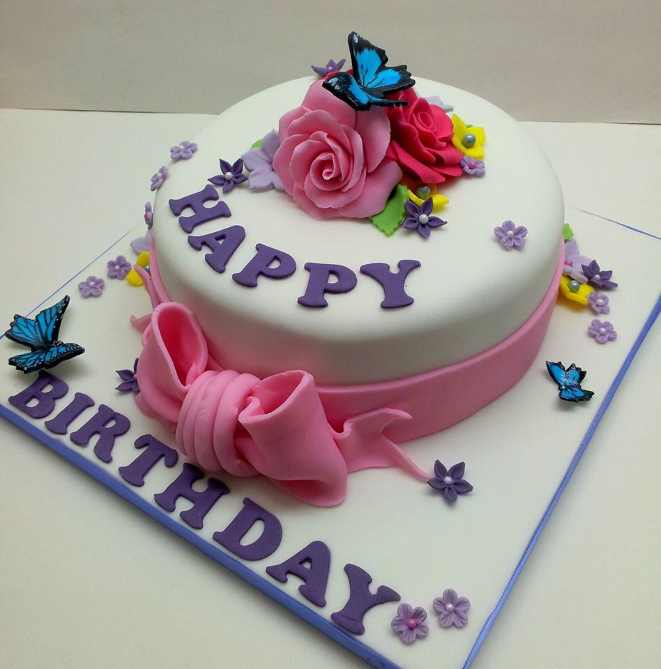 A white birthday cake decorated with pink sugar ribbon and flowers