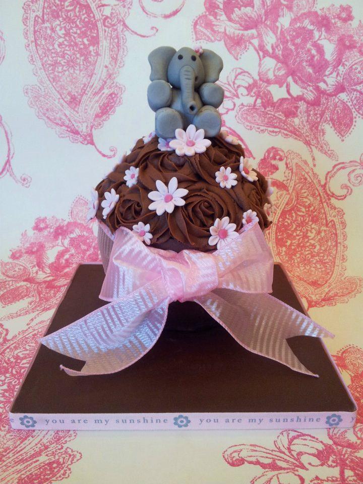An elephant on a chocolate cake decorated with pink ribbon