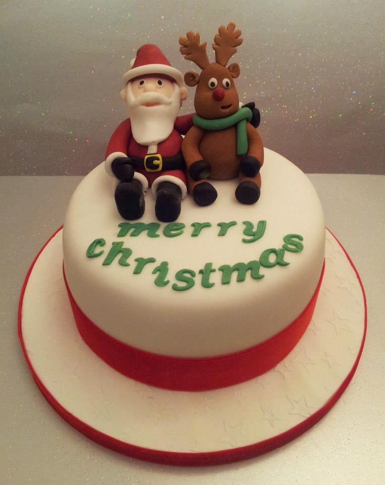 Santa and Rudolph figures on a white and red Christmas cake