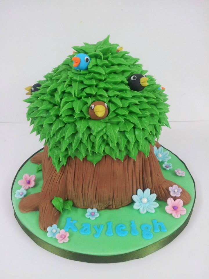 A cake shaped like a tree, with birds peeping out through the branches