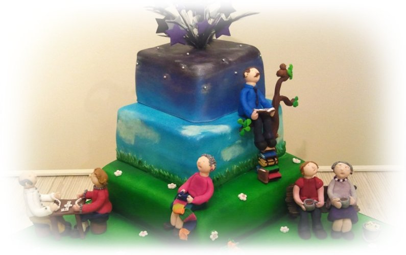 A cake with few man and woman on it