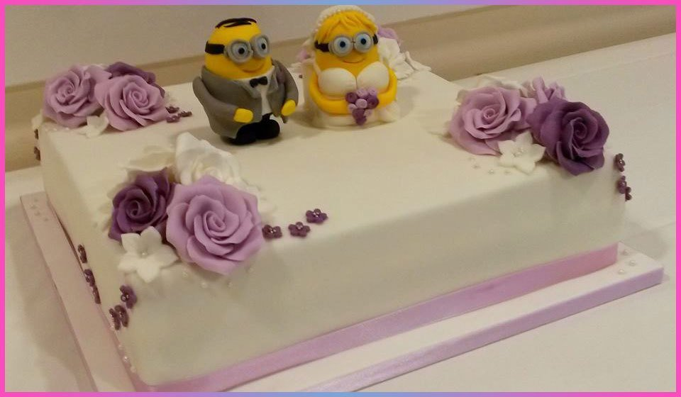 Wedding cake decorated with purple flowers, and Minion bride and groom figures