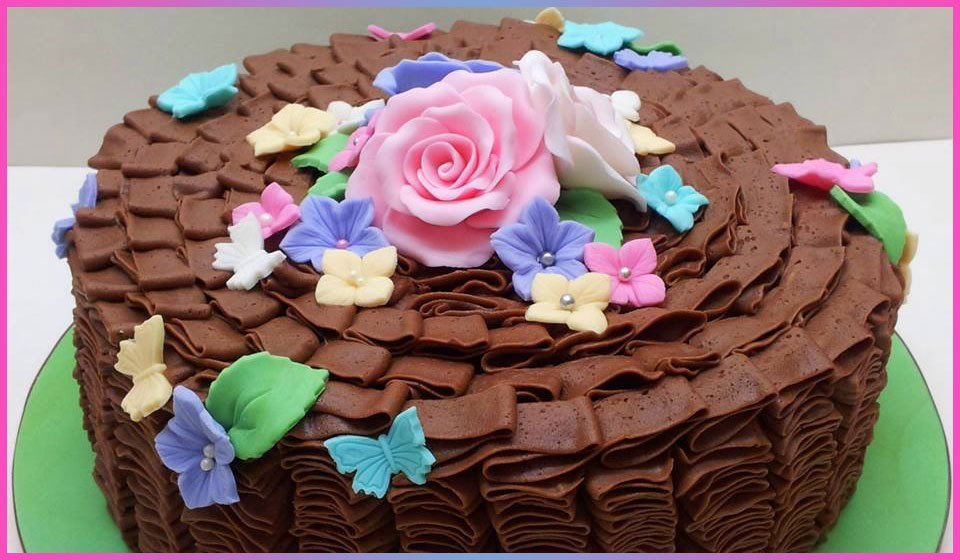 A chocolate ripple cake decorated with sugar flowers