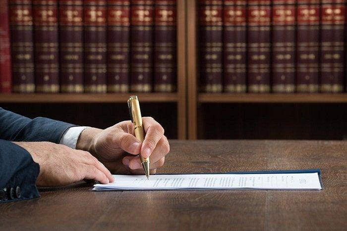 avvocato firma un documento all'interno di uno studio