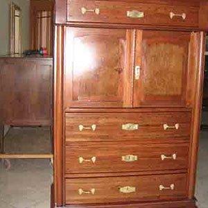 un mobile in legno con dei cassetti e delle maglie dorate