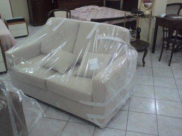 Stanza con caminetto, grande sofà rosso, poltrone rosso, poltrone chiaro , tavola bassa in legno chiaro e tre piccoli mobili ausiliari