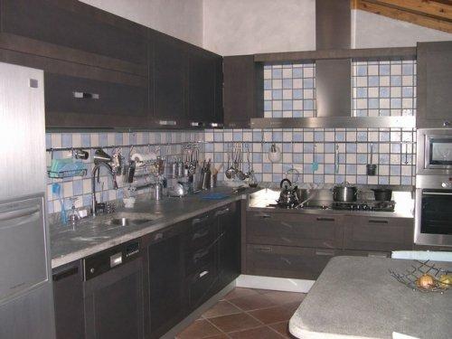 Cucina di legno,acciaio e marmo completamente accessoriata.Sottolinea l'abbinamento di piastrelle bianche e blu della parete