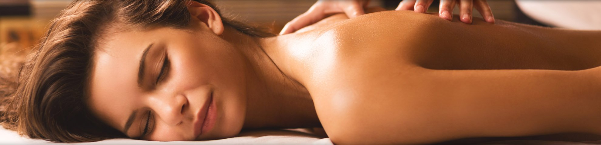 una donna sdraiata a pancia in giù e due mani che le massaggiano la schiena