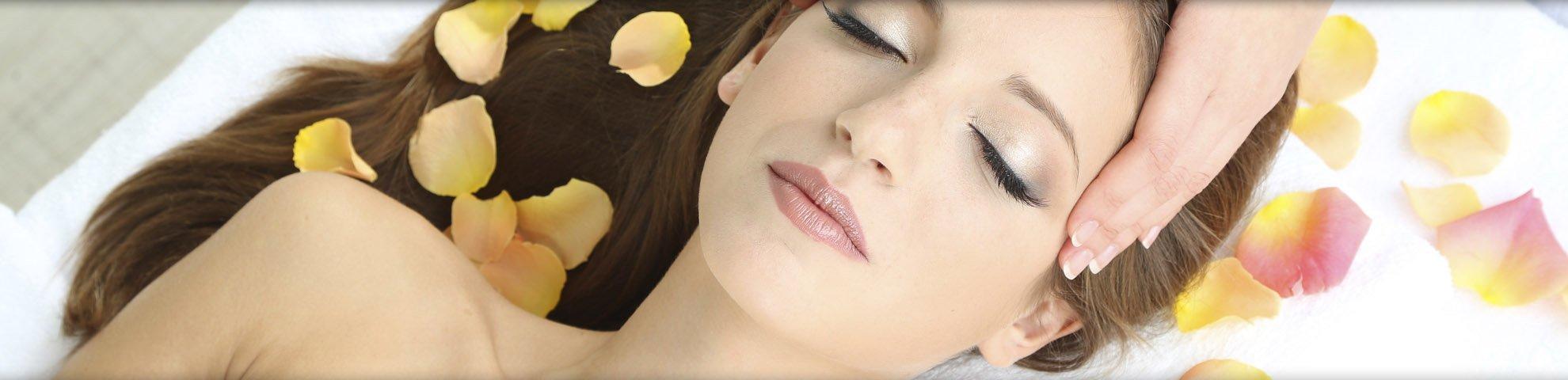 una donna sdraiata su un lettino con dei petali e due mani che le  massaggiano le tempie