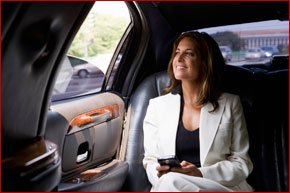 Lady wearing a suit in a car with her phone in her hand