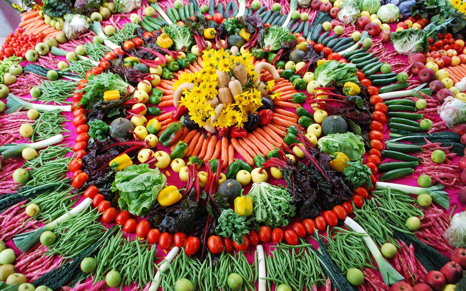 Della frutta, della verdura disposte a forma di fiore e dei fiori gialli al centro