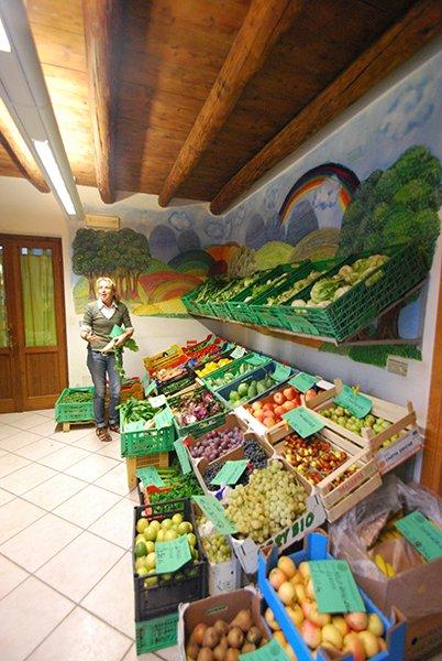 Delle casssette di frutta e verdura all'interno di un negozio e una donna davanti in piedi