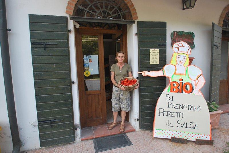 una donna con un cestino di pomodori e sulla destra un rilievo di cartone di una donna vestita da cuoco