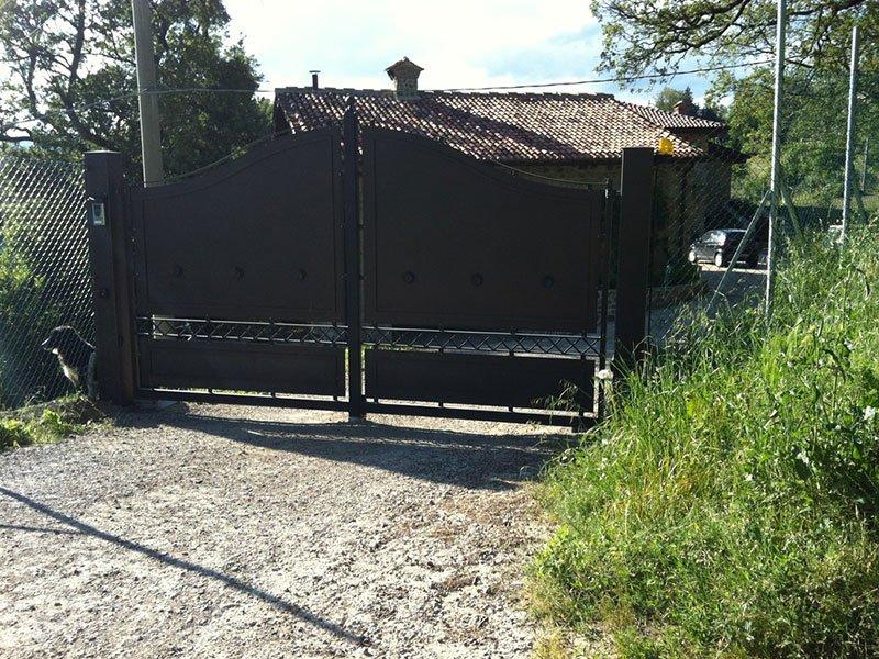 Porta di accesso alla proprietà fatta in metallo nero, ondulata nella parte superiore, con design a vomeri nella parte inferiore