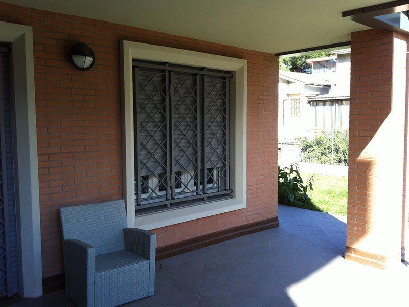 Elegante protezione di finestra progettata in tre pannelli di metallo nero e la cui progettazione è in linee diagonali
