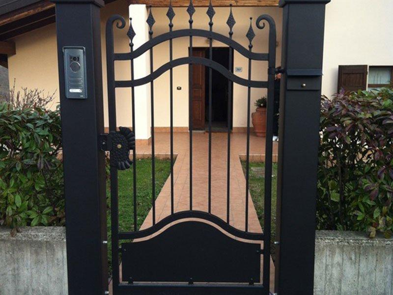Porta di ingresso alla proprietà in metallo nero progettata con sbarre di lancia facendo un'onda