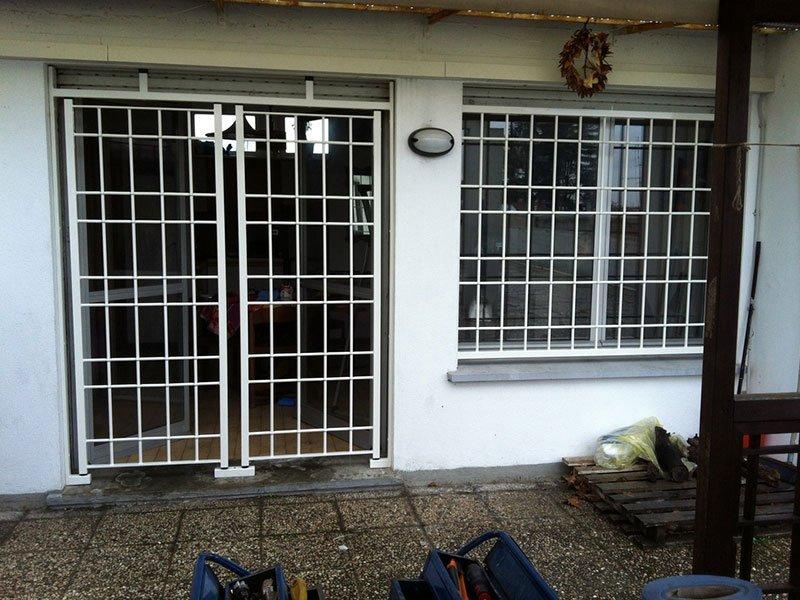 Protezioni della porta e finestra fatte in metallo bianco con forme quadrate e rettangolari