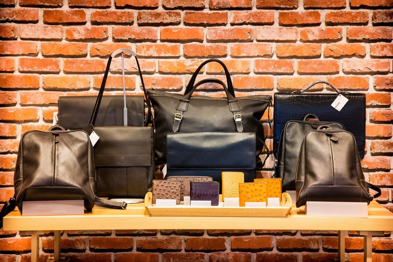 borse e portafogli di pelle su un tavolo di fronte ad un muro di mattoni