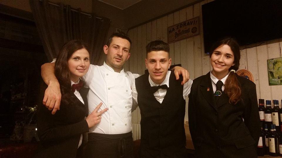 4 ragazzi abbracciati con uniformi del ristorante, in posa per una foto