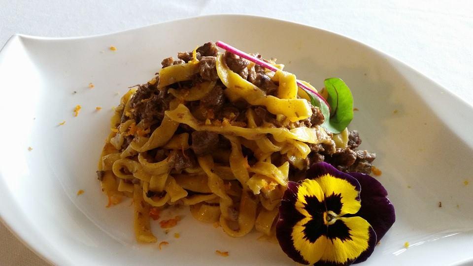 piatto di tagliatelle con ragu' di salsiccia e una violetta