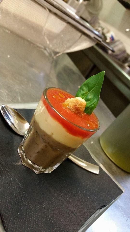 un bicchiere con una mousse tricolore, marrone beige e rossa con foglia di basilico e crostino sulla cima